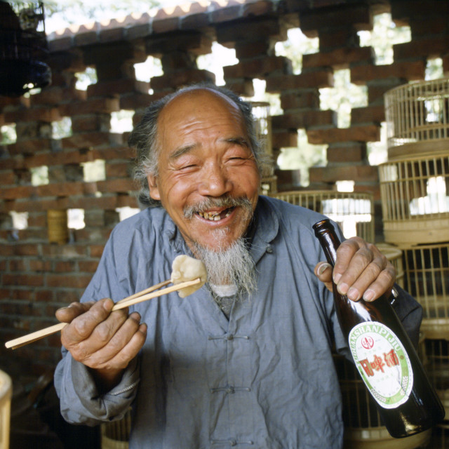 """Man eating with chopsticks & drinking beer, Beijng, China"" stock image"