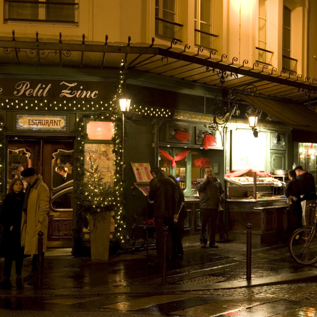 """People shelter from rain at night on street corner outside traditional Le..."" stock image"