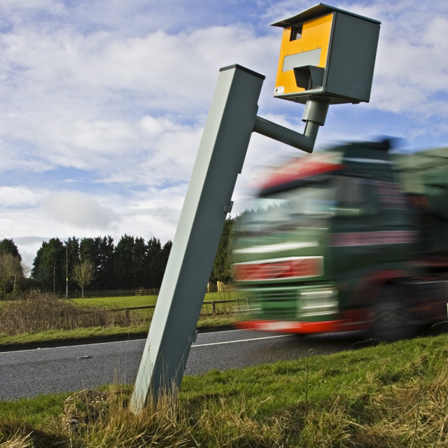 """Traffic passes vandalised Gatso speed camera unable to function on A40 road,..."" stock image"