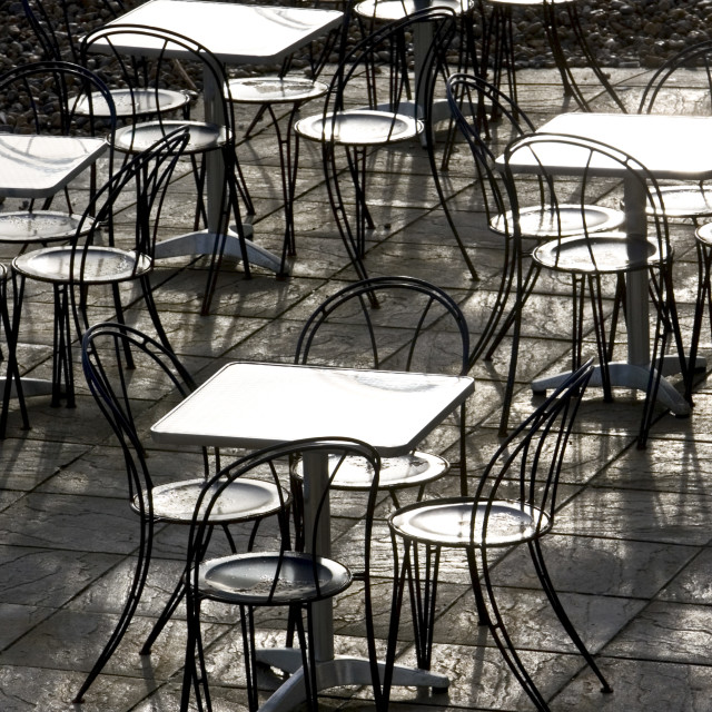 """""""Deserted tables and chairs out of season on Brighton beach, South Coast, ..."""" stock image"""