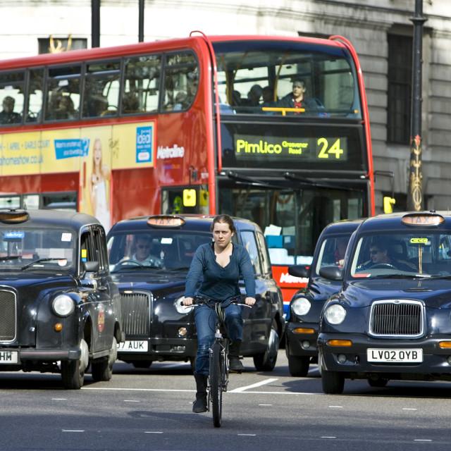 """Biker in front of heavy traffic in Trafalgar Square, downtown London city..."" stock image"