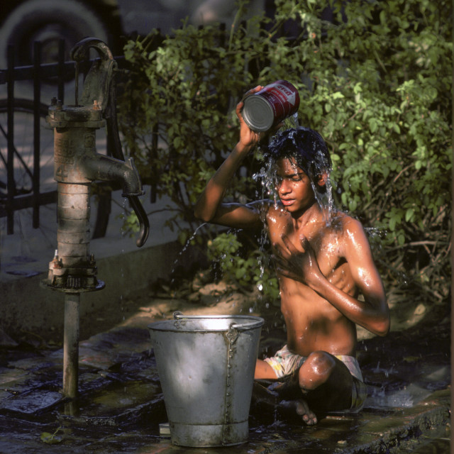 """Boy having an early morning wash from a water pump in Delhi, India."" stock image"