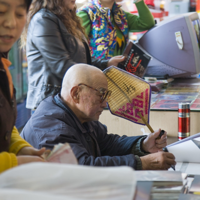 """Mr Yang Peiyan, the farmer who found the Terracotta Warriors, signs books in..."" stock image"