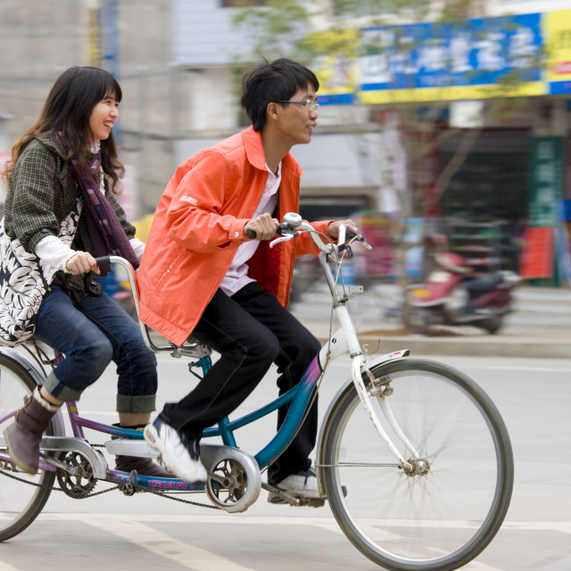 """Couple on a tandem bicycle in Yangshuo street, China"" stock image"