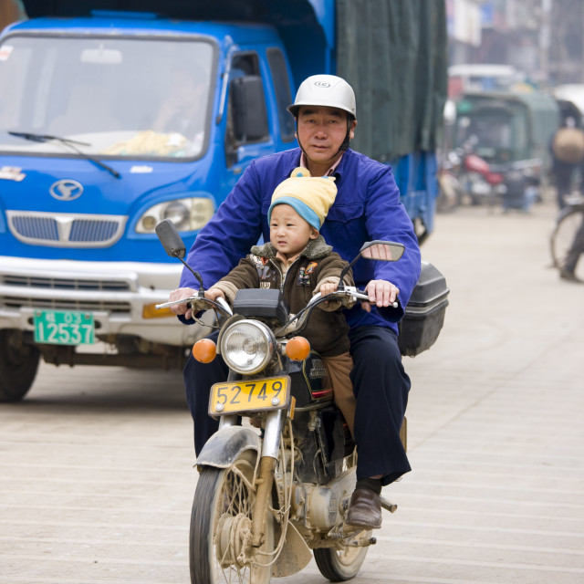 """""""Man and child on a motorbike on market day in the town of Baisha, near..."""" stock image"""