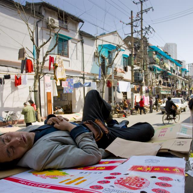 """Man sleeps on cardboard in Zi Zhong Road, old Shanghai, China"" stock image"