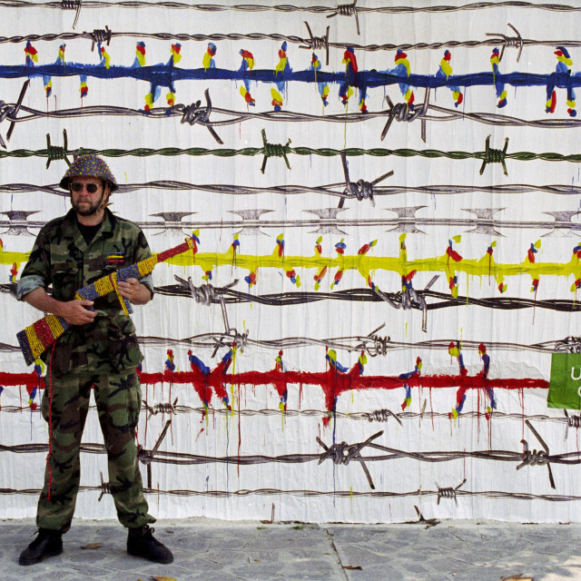 """""""Man dressed as soldier with coloured weapon in front of United Colors of..."""" stock image"""