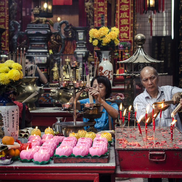 """A man and women light incense sticks during Chinese New Year celebrations,..."" stock image"
