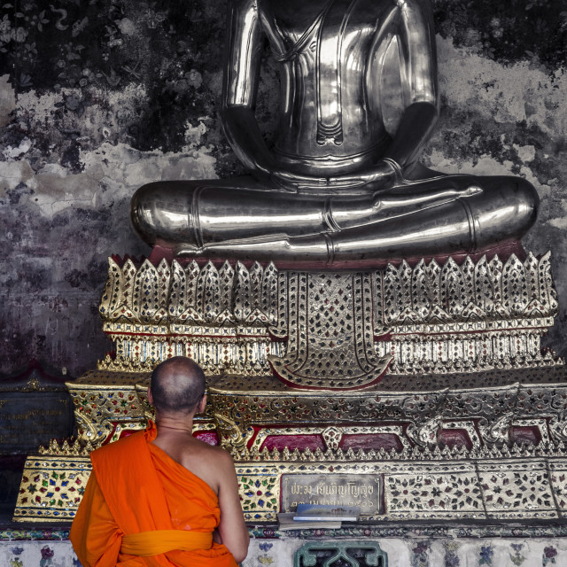 """""""A monk prays in front of a golden Buddha, Wat Suthat, Bangkok, Thailand,..."""" stock image"""