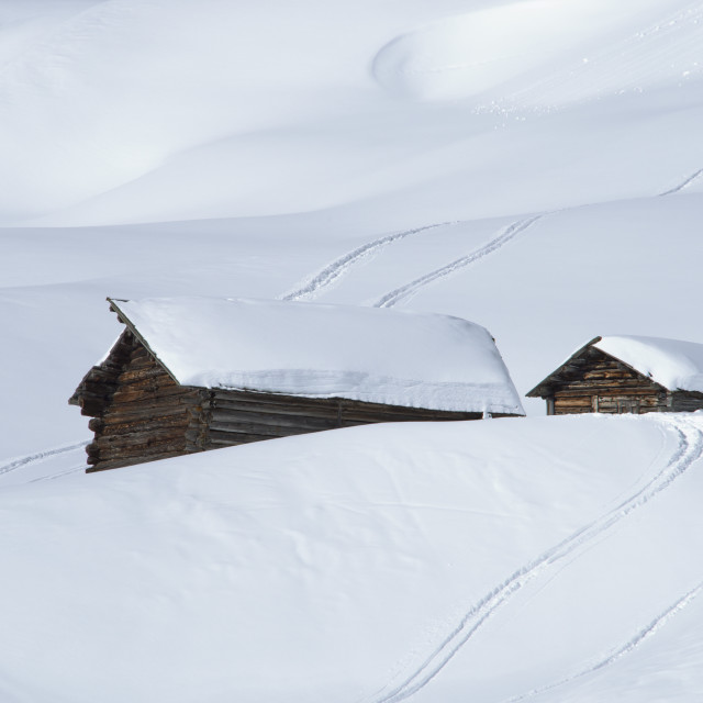 """""""Two old wooden barns surrounded by deep snow and ski tracks in the Dolomites,..."""" stock image"""
