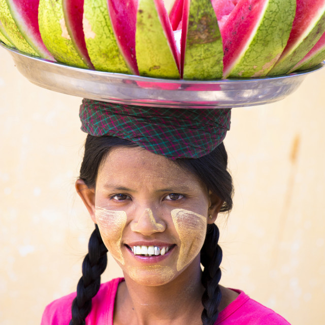 """""""Local woman with Thanakha traditional face painting, carrying a tray of..."""" stock image"""