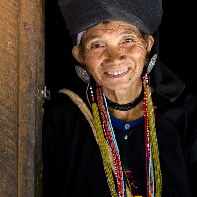 """Woman of the Ann tribe in traditional black dress and colourful beads in a..."" stock image"