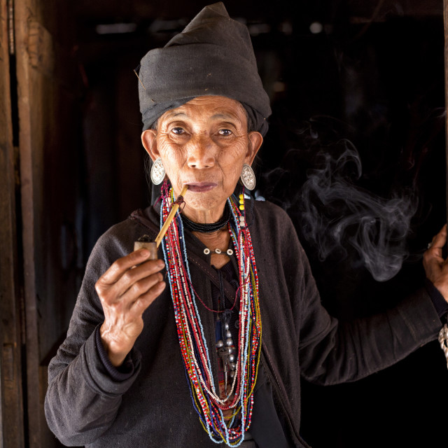 """""""Woman of the Ann tribe in traditional black dress and colourful beads smoking..."""" stock image"""