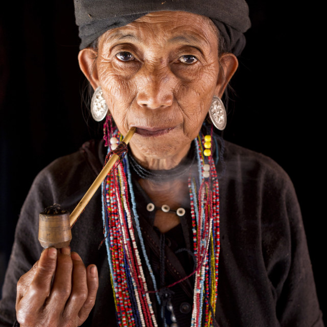 """Woman of the Ann tribe in traditional black dress and colourful beads smoking..."" stock image"