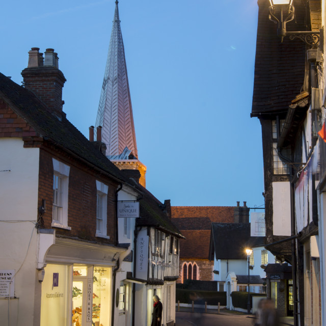 """The spire of parish church stands at dusk above a historic street in..."" stock image"