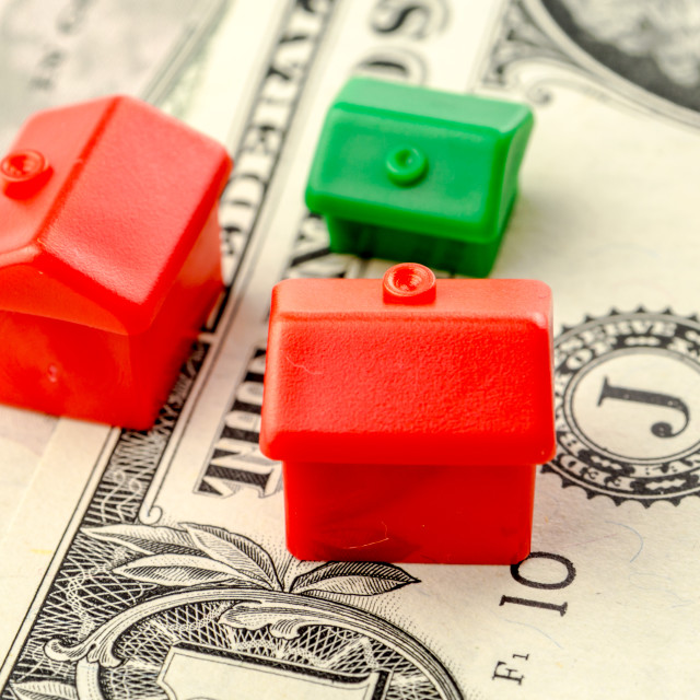 """three little houses made of plastic are laying on one dollar banknote"" stock image"