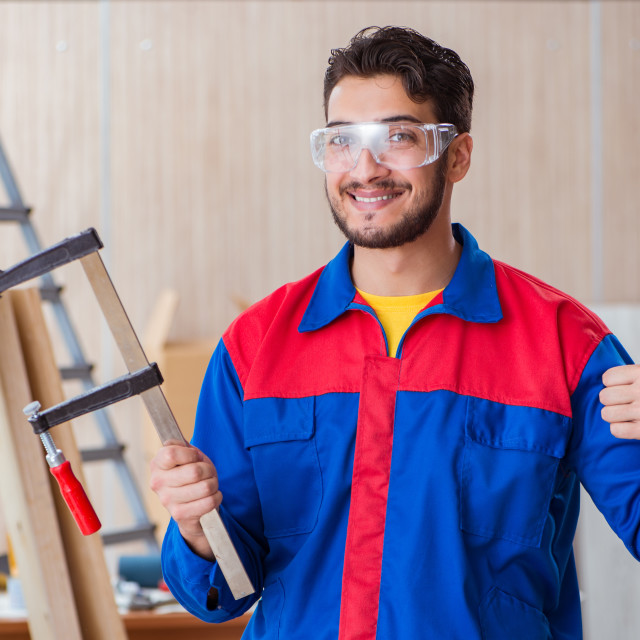 """The young repairman carpenter working with clamps"" stock image"