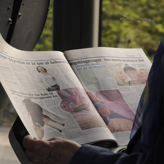 """BUS PASSENGER READING FREE NEWS PAPER"" stock image"
