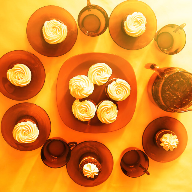 """""""Decorated table with fresh cupcakes warm background"""" stock image"""