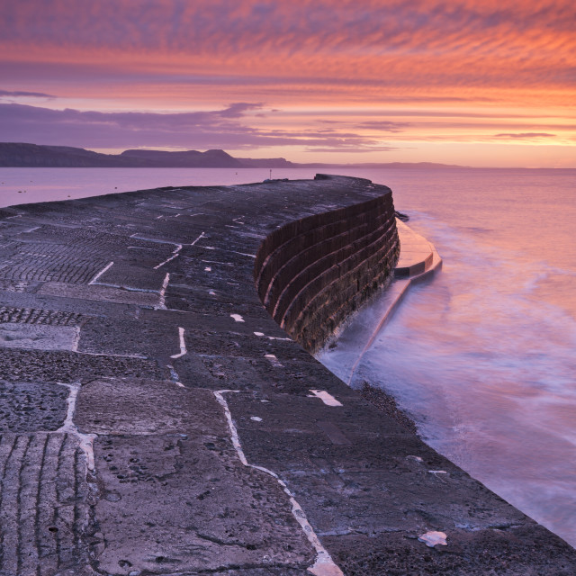 """Spectacular winter sunrise above The Cobb harbour wall, Lyme Regis, Dorset,..."" stock image"