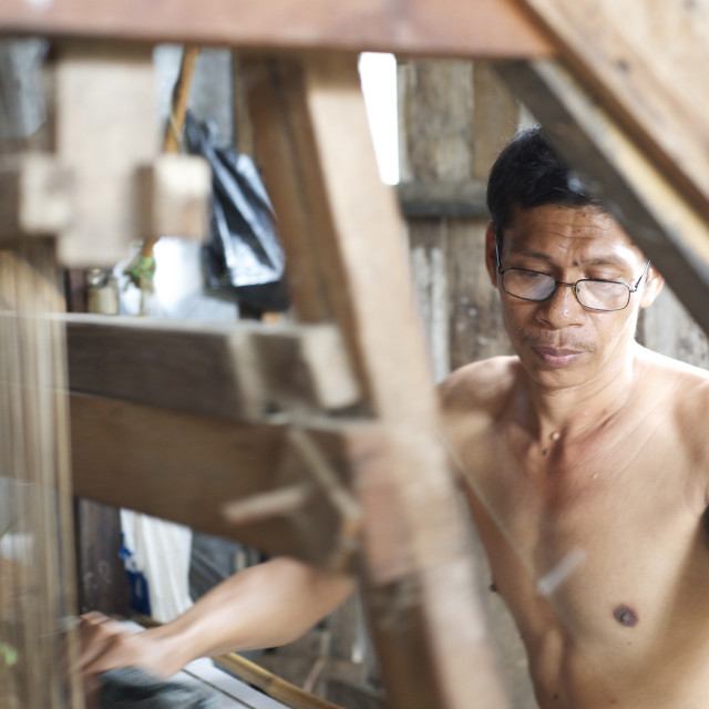 """Silk weaver working on a traditional wooden loom in a factory in Pekalongan,..."" stock image"