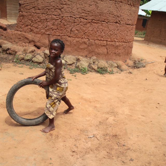 """African girl having fun rolling an old tyre, Tori, Benin, West Africa, Africa"" stock image"