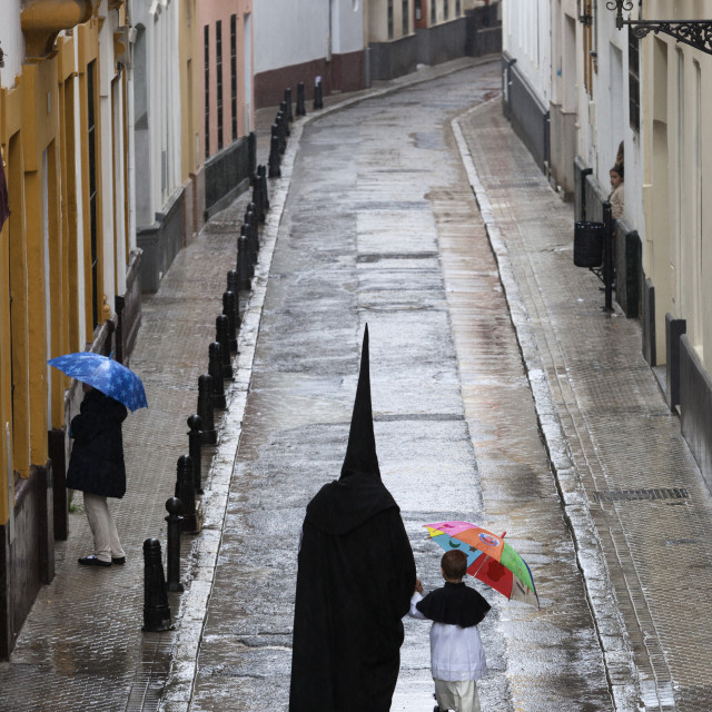 """Penitents during Semana Santa (Holy Week) along rainy street, Seville,..."" stock image"