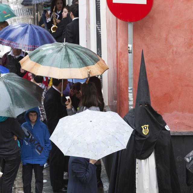 """Penitent during Semana Santa (Holy Week) along rainy street, Seville,..."" stock image"