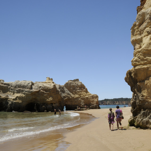 """People walking and paddling near sandstone cliffs and rocks at Praia da Rocha..."" stock image"