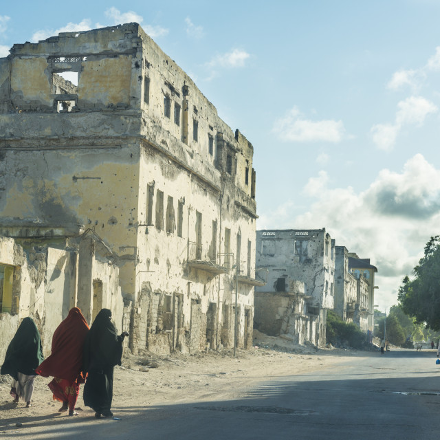 """Somali women walking through the streets of the destroyed houses of..."" stock image"