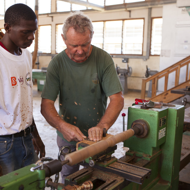 """A VSO volunteer teaching how to use a lathe during a VSO woodwork vocational..."" stock image"