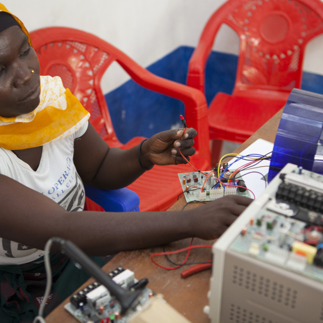 """""""A female solar engineer, known as a solar mama, works on the printed circuit..."""" stock image"""