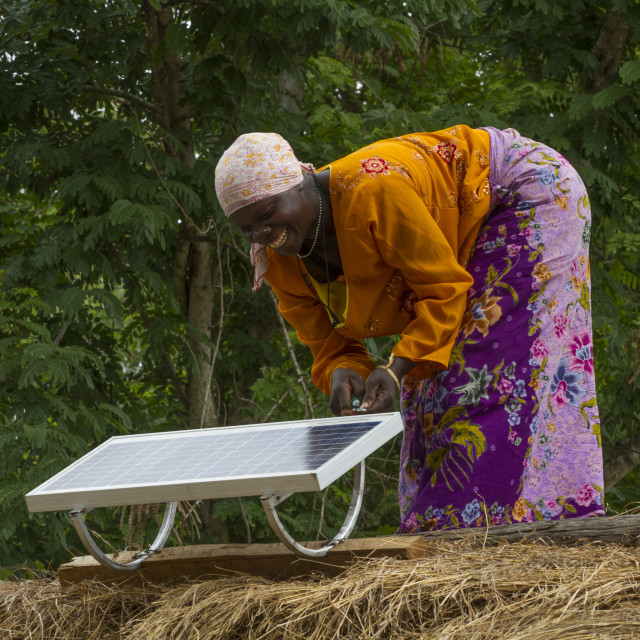 """""""A woman, known as a Solar Mama, fixes a solar panel to the top of a..."""" stock image"""