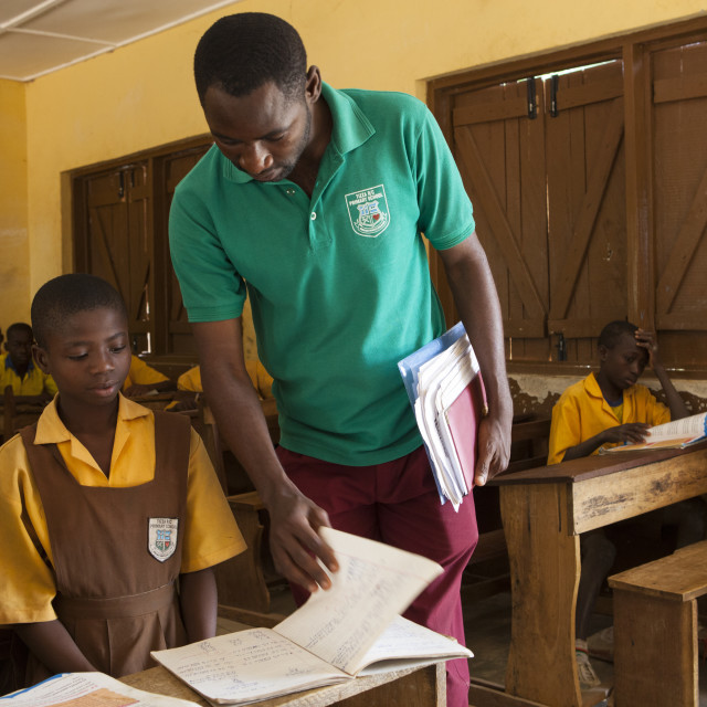 """A male teacher teaching a classroom of children at a primary school in Ghana."" stock image"