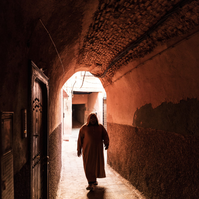 """""""Local man dressed in traditional Djellaba walking through archway in a street..."""" stock image"""