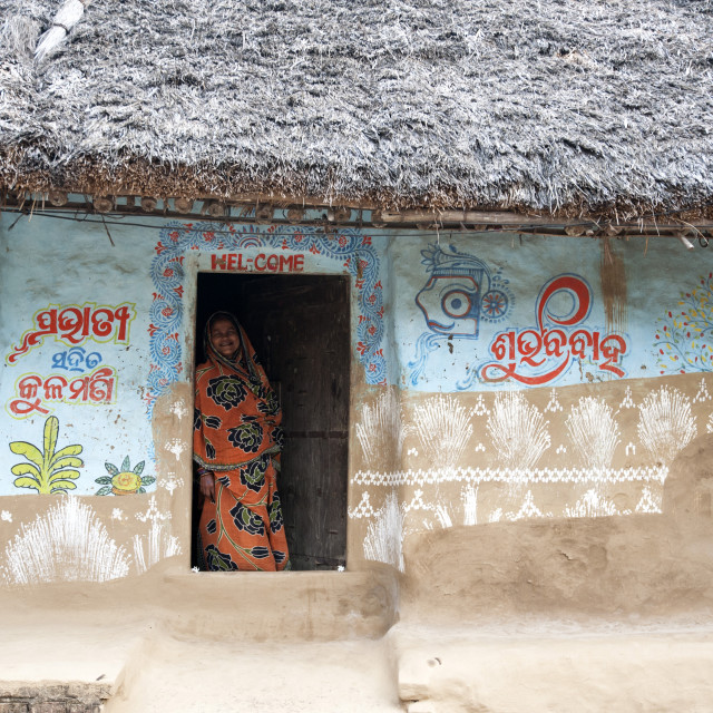 """""""Woman at the door of traditional mud walled Odisha village house decorated..."""" stock image"""