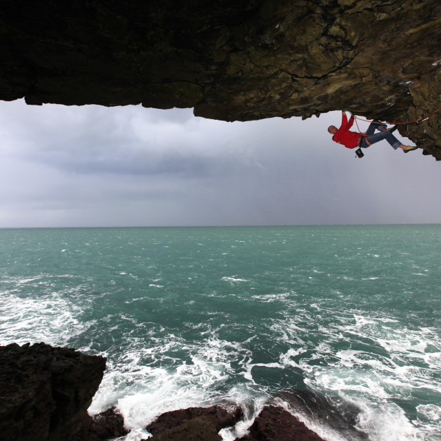 """A climber scales a sea cave near Swanage, Dorset, England, United Kingdom,..."" stock image"