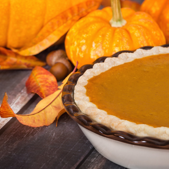 """Pumpkin pie with pumpkins and autumn decorations on rustic table"" stock image"