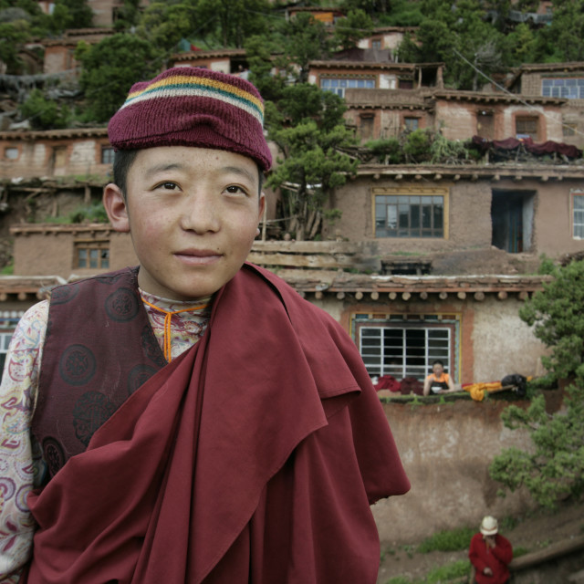 """Nun in front of earthen homes, Dechenling Nunnery, Tibet"" stock image"