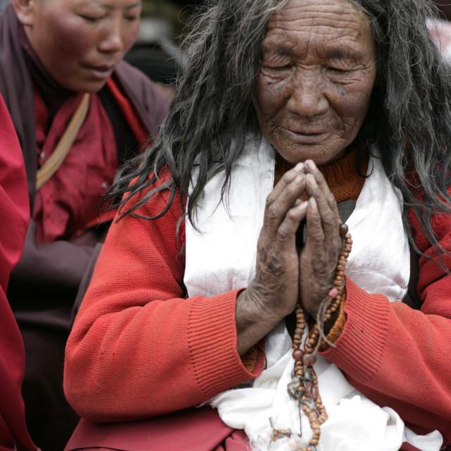 """Nun in prayer, Dechenling, Nangchen, Tibet"" stock image"