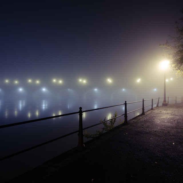 """""""Riverbank and bridge at night with misty atmosphere over city view"""" stock image"""