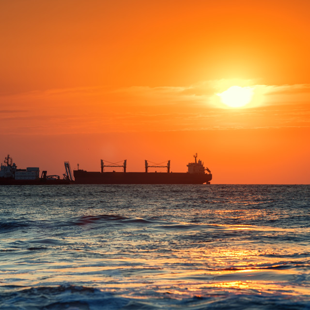 """""""Sun setting at the sea with sailing cargo ship, sunrise view"""" stock image"""