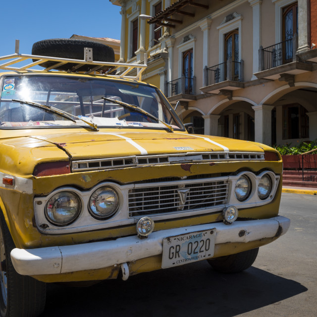 """Granada, Nicaragua - April 2, 2014: Old yellow pick-up truck parked in front of a colonial building in the city of Granada in Nicaragua."" stock image"