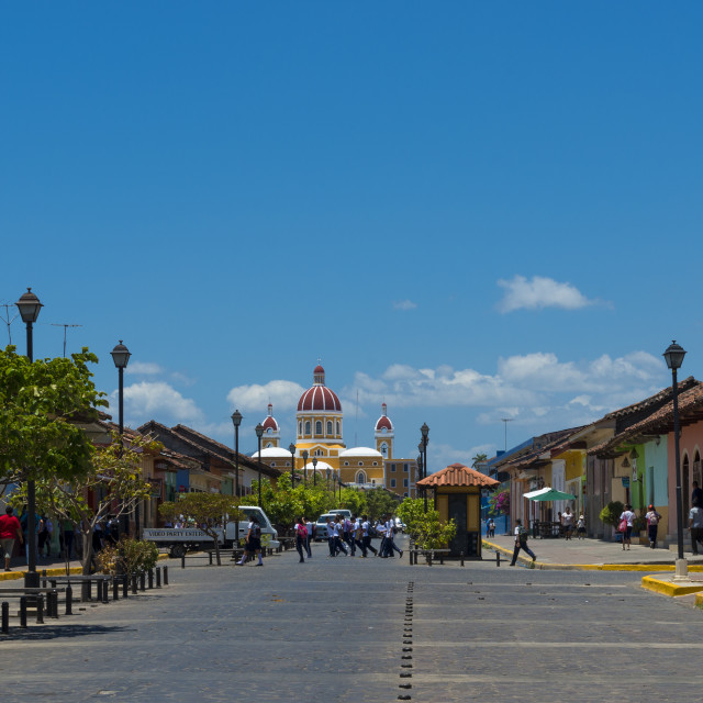 """Granada, Nicaragua - April 2, 2014: View of a street with colonial building and the colorful Our Lady of the Assumption Cathedral on the background in the city of Granada, Nicaragua."" stock image"