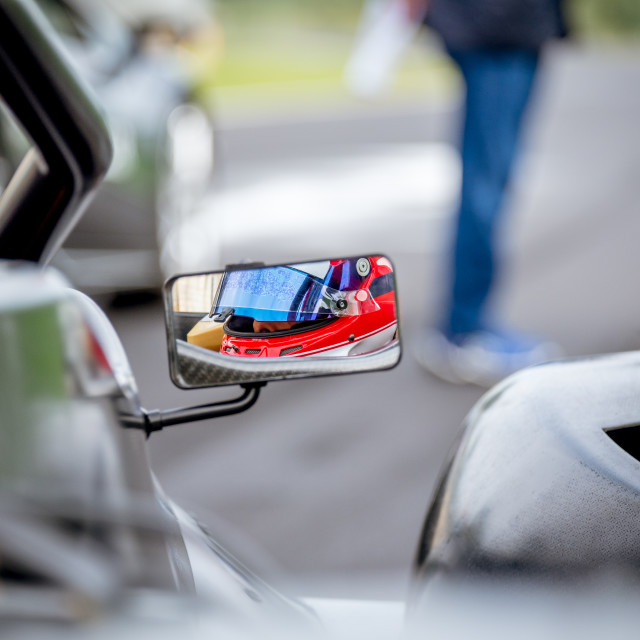 """Motorsport car driver detail on rear view mirror"" stock image"