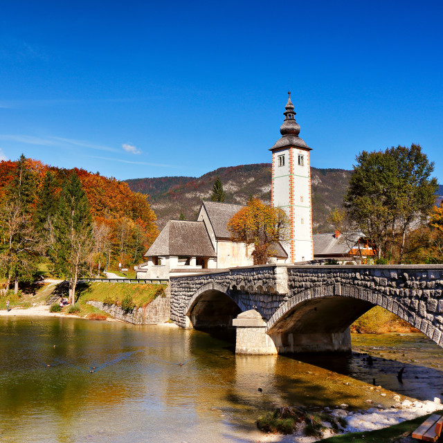 """Colorful autumn day in ancient village with old bridge and churc"" stock image"