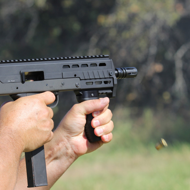 """Man firining submachine gun mini"" stock image"