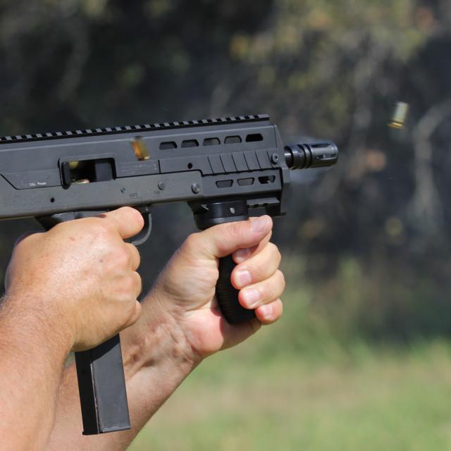 """Closeup of automatic machine gun will shellcasings flying away"" stock image"