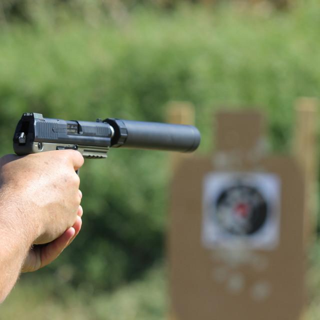 """Man testfiring pistol with silencer"" stock image"