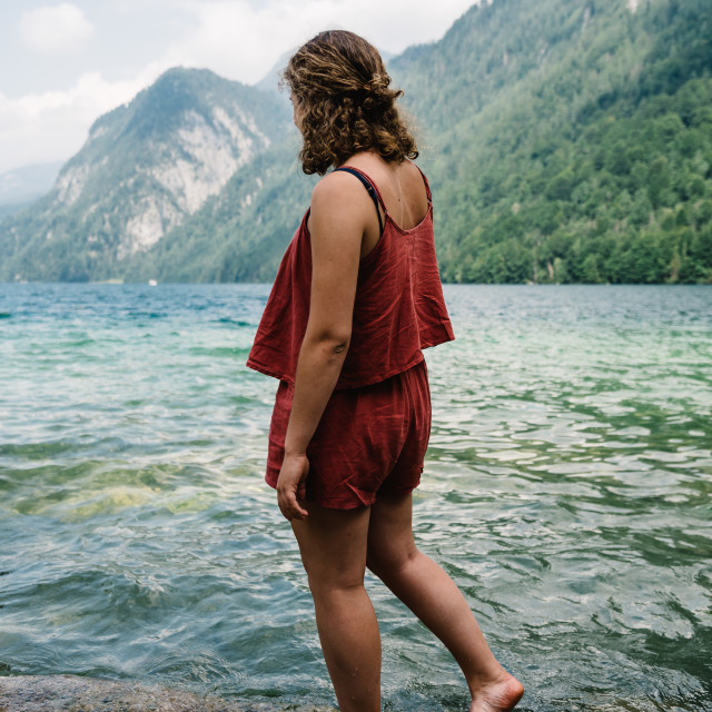 """Barefoot young woman standing on rock looking at beautiful lake"" stock image"